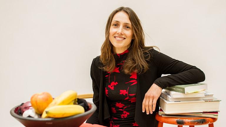 P4-dietisten Marléne Hedelin lutar sig mot några böcker bredvid en fruktskål