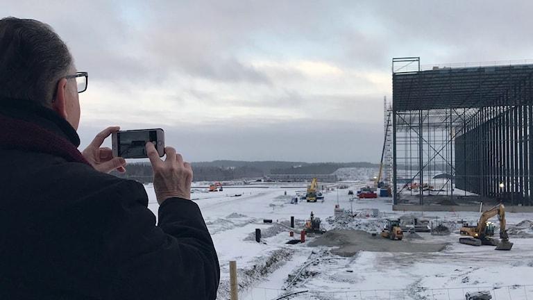 Pensionären Rune Nyström fotar Northvoltfabriken från utsiktsplatsen