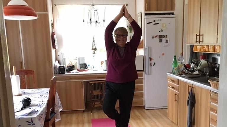Laila Engman visar trädet på sin rosa yogamatta i köket