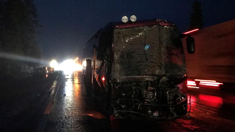 En röd buss med krockad frnt. Mörkt ute och andra fordon som passerar.