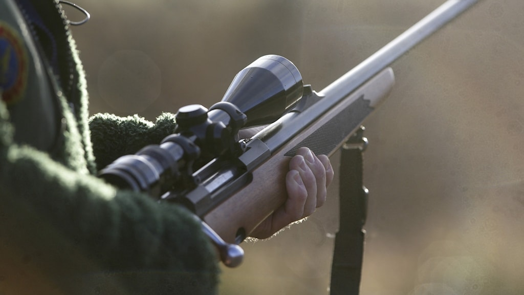 Bild på person som håller i ett jaktgevär.