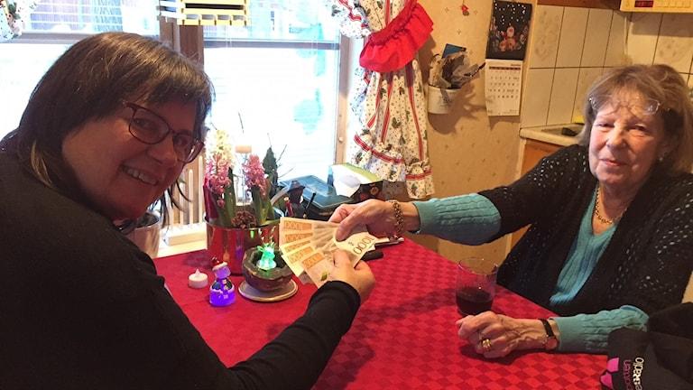 Ewa skänker pengar till behövande familjer. Diakon Kristina Blomberg tar emot.