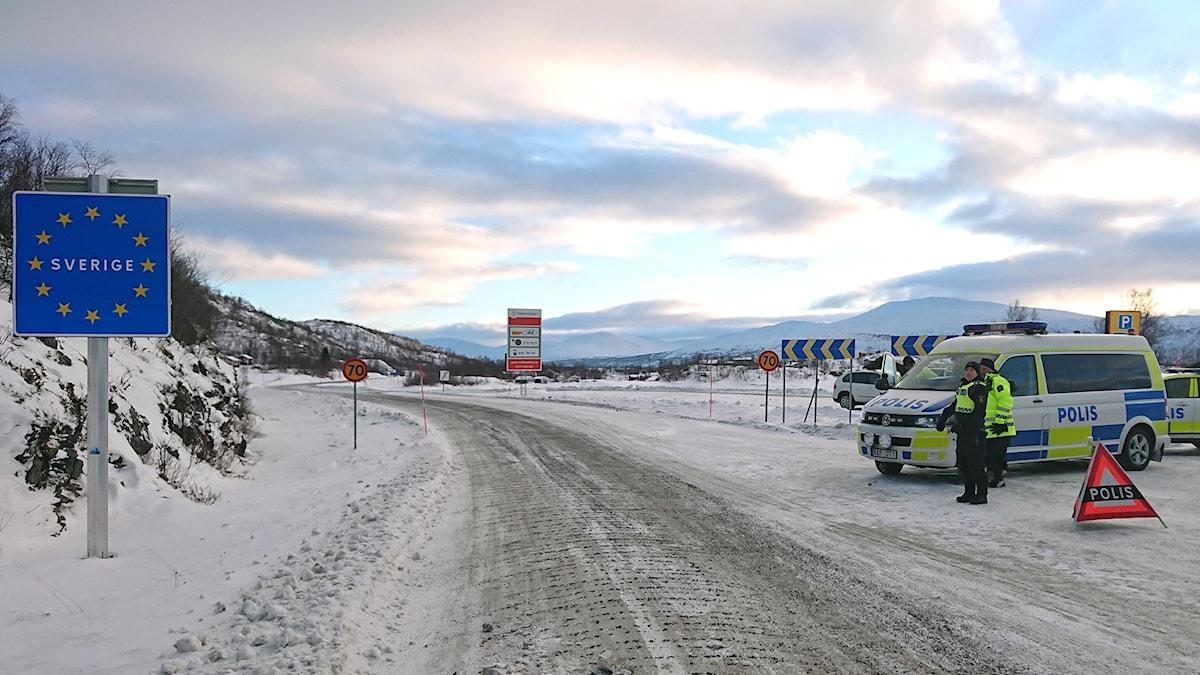 Gränsövergång på fjället, vinterväg och två polisbilar.