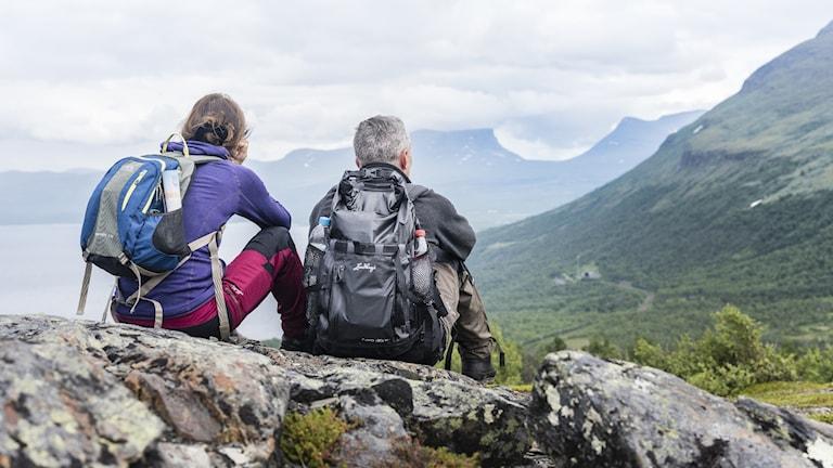 Ett par pausar under fjällvandring i Björkliden med utsikt över Lapporten