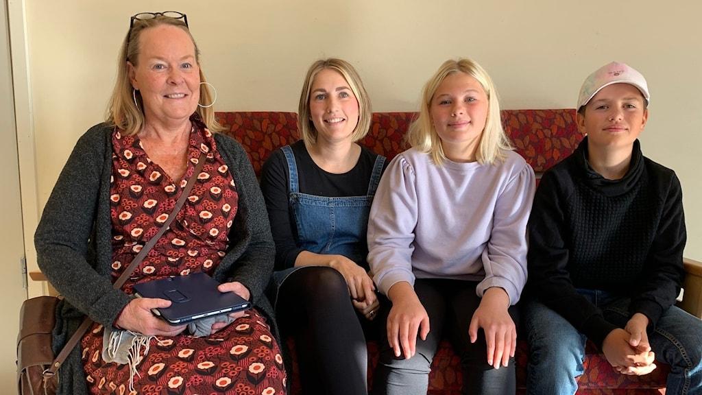 fyra personer sitter i en soffa