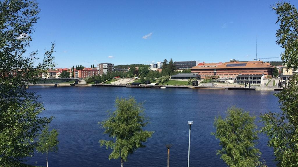 Solen vilar över Skellefteås kommunhus och älvsbrinken på andra sidan älven.