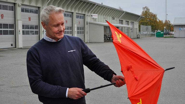 Fredrik Thoms, säkerhetssamordnare på Umeå kommun, fäller upp ett paraply