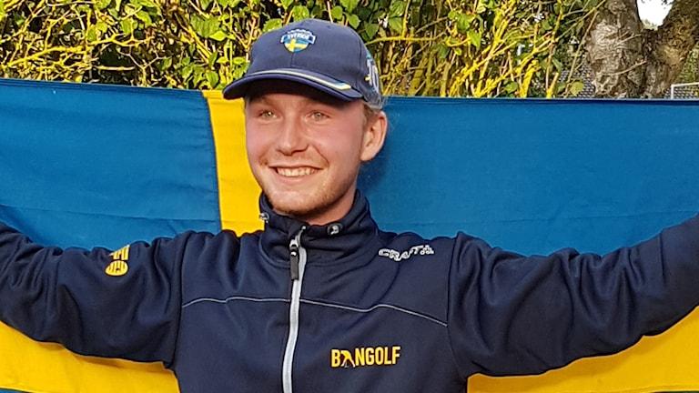 En glad, kepsklädd kille framför en svensk flagga.