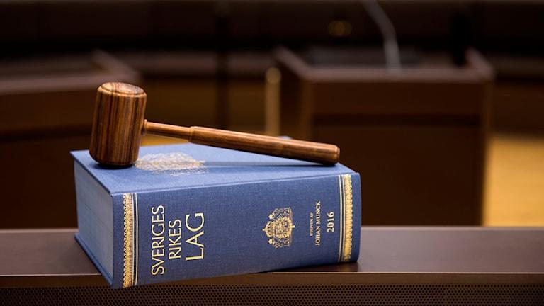 En bild på en lagbok och en domarklubba