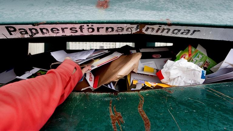 En arm sträcks ut för att slänga kartonger i en grön containar med texten pappersförpackningar.