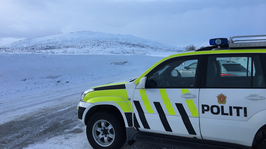 Norsk polisbil står på parkeringsficka mitt på fjällen och kontrollerar gränsöverfarten till Norge.