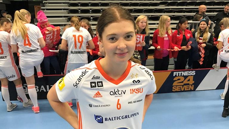 Innebandyspelaren Tova Eriksson efter en seger mot Iksu. I bakgrunden skriver hennes lagkamrater autografer och unga flickor väntar på sin tur.