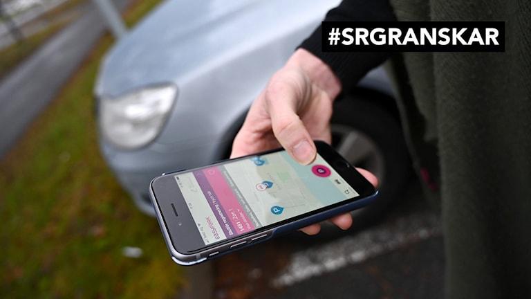 Närbild av en hand som håller i en smartphone med parkeringsapp igång.