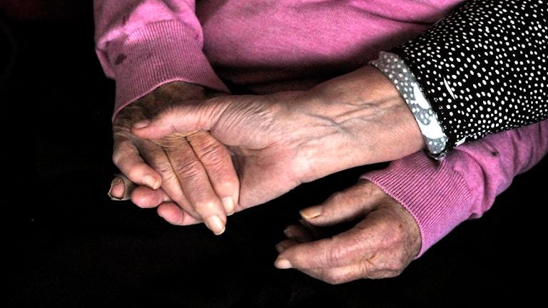 Kvinna håller en äldre kvinnas händer. Foto: Hasse Holmberg/Scanpix.