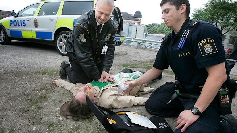 Förmågan att kommunicera och förstå andra kan vara viktigt för blivande poliser. På bilden tränar en polis och en taxichaufför på första hjälpen.