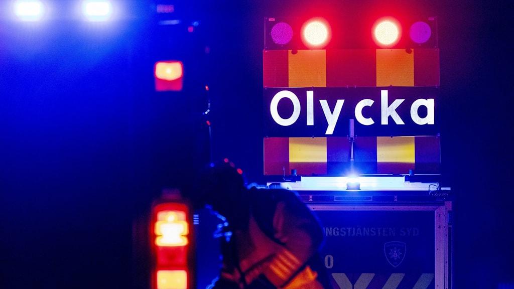 En räddningsarbetare i mörkret vid en olycksplats, framför en vägskylt där det står olycka