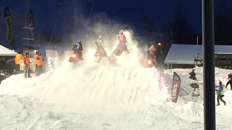 Flera skotrar i bredd uppför ett hopp på en tävling i stadioncross. Snön yr om förarna.