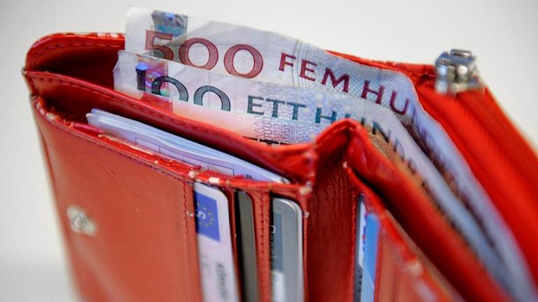 En plånbok full med pengar, bankkort och körkort. Foto: Jessica Gow/Scanpix.