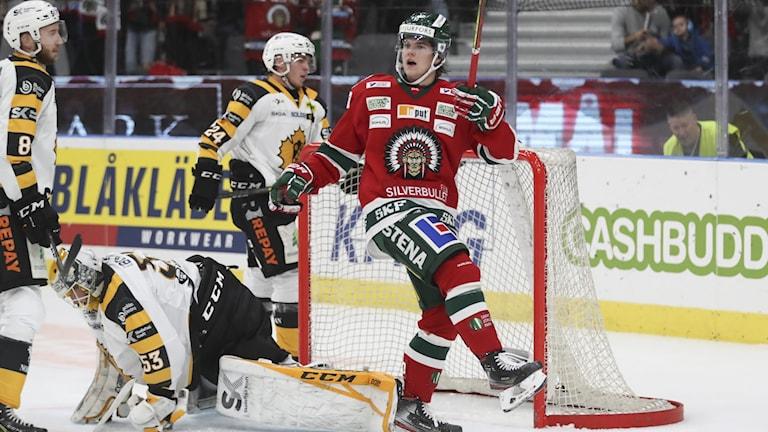 Frölundaspelare jublar över storseger över Skellefteå AIK, Vitklädda Skellefteåspelare uppgivna i bakgrunden.