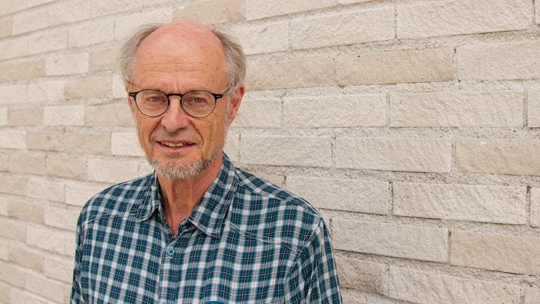 Bengt Järvholm professor i yrkes- och miljömedicin vid Umeå universitet mot en tegelvägg