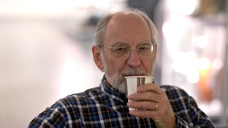 Bosse bildoktor med en kopp kaffe i handen.