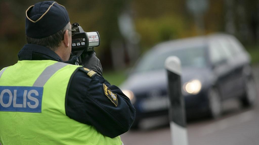 En polis kontrollerar trafiken med en hastighetskamera