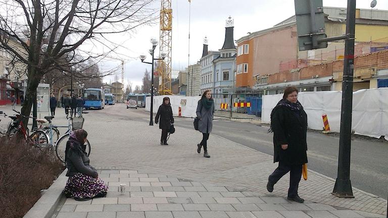 Kvinna sitter på en gata och tigger, människor går förbi