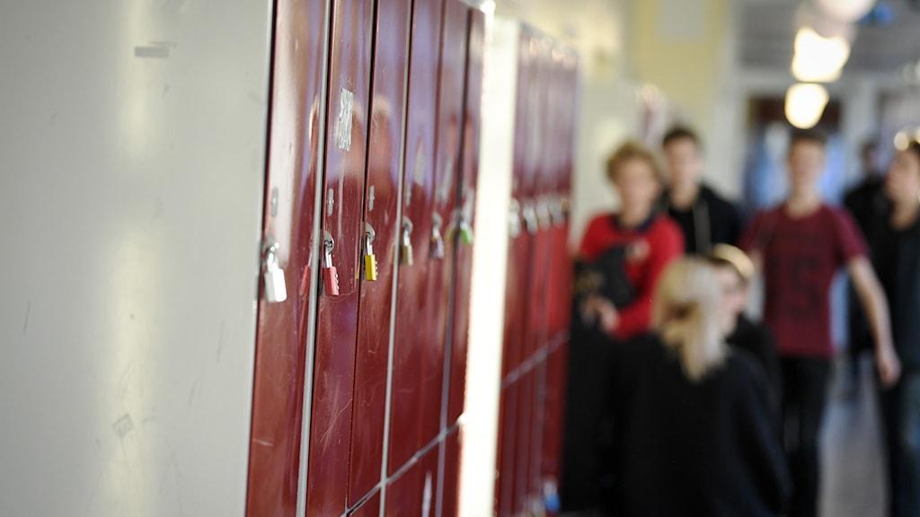 Genrebild på skåp i skolkorridor. Elever i bakgrunden.