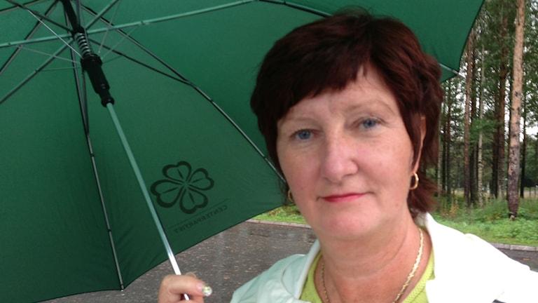 Kvinna under grönt paraply med Centernsymbol