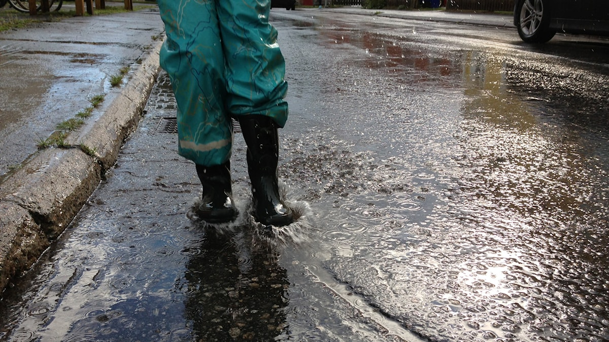 Ett barn plaskar i regn. Foto: Erica Dahlgren/Sveriges Radio