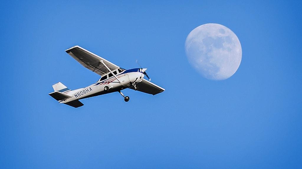 Ett Cessna 172 korsar himlen framför månen.