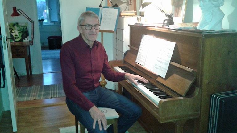 Man som sitter vid ett piano