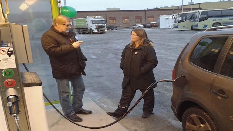 Tekniska nämndens ordförande Ola Burström tankar bilen åt Ulrika Lindkvist. Foto: Linnea Hedelilja