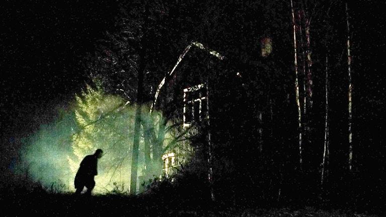 Mörk mystisk bild, ensam man vid ödehus