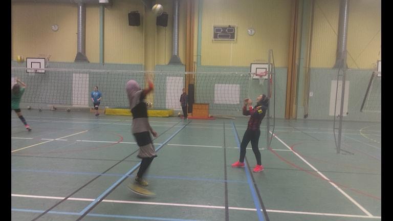 Tjejer tränar volleyboll, några av dem i hijab (muslimsk sjal).