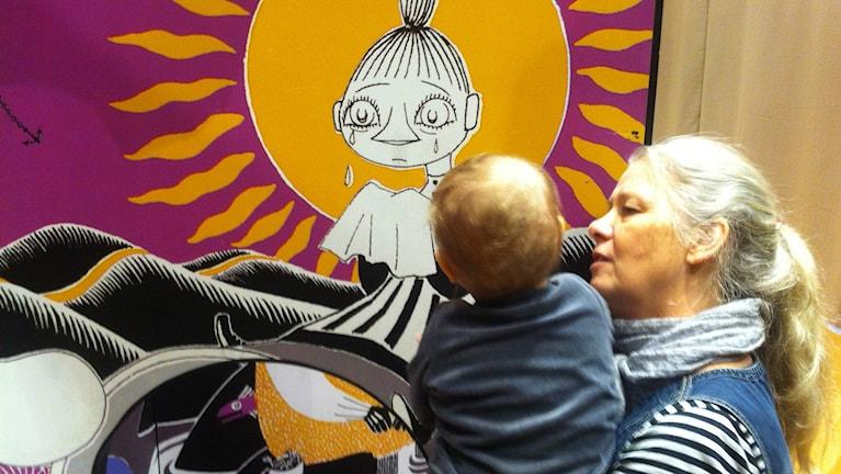 Maria Nilsson visar att Mymlan gråter för sitt barnbarn. Foto: Joakim Silverdal/SR.