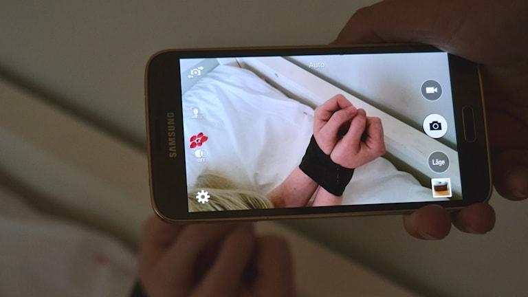 Bild på ihoptejpade händer i en säng. Foto: Marilén Karlsson