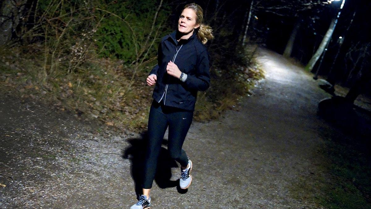 Kvinna springer i mörkret på ett motionsspår. Foto: Claudio Bresciani/TT
