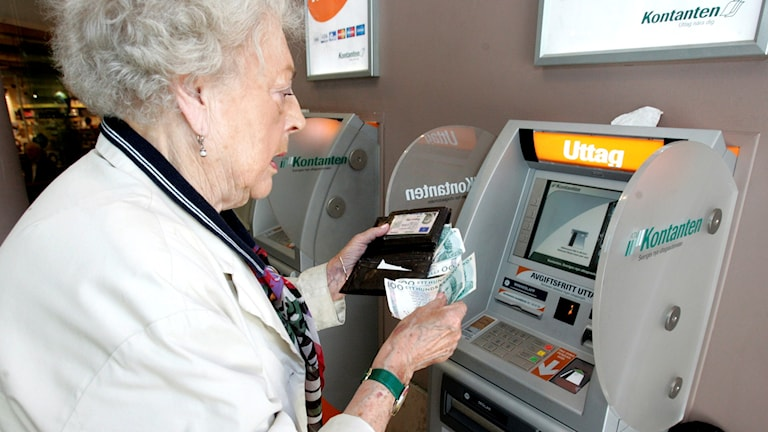 Äldre kvinna tar ut pengar i en bankomat. Foto: Bertil Ericson / TT