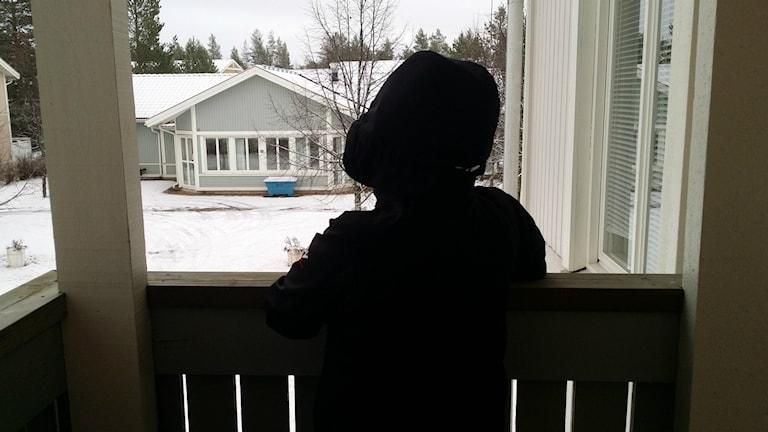 En anonym kvinna tittar ut över en gård