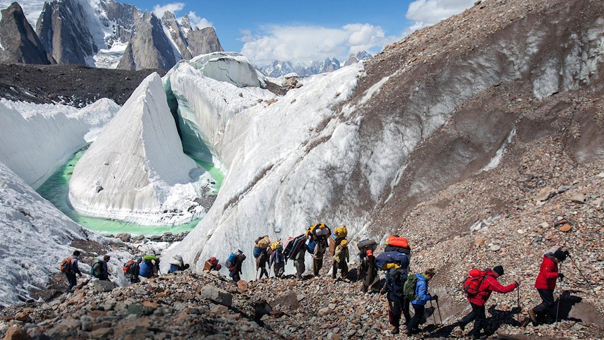 """En rad människor med packning vandrar uppför berg i Himalaya. En bild från filmen """"K2. Touching The Sky"""" av regissören Eliza Kubarska."""