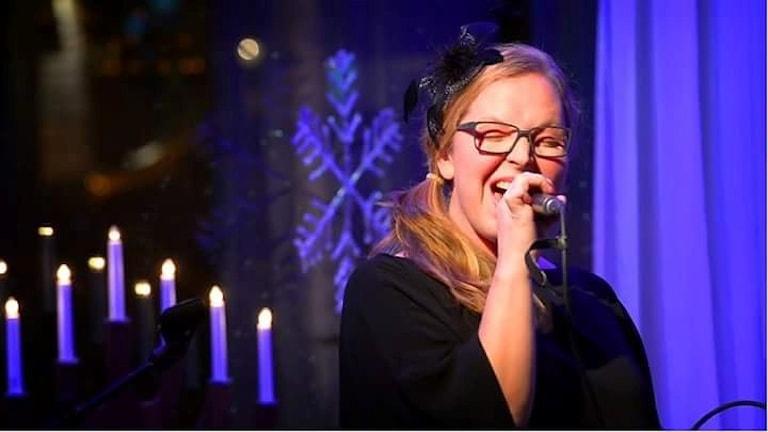 Sångaren Hanna Ögren sjunger i svart klänning vid ljusstake. Foto: Johan Eriksson.