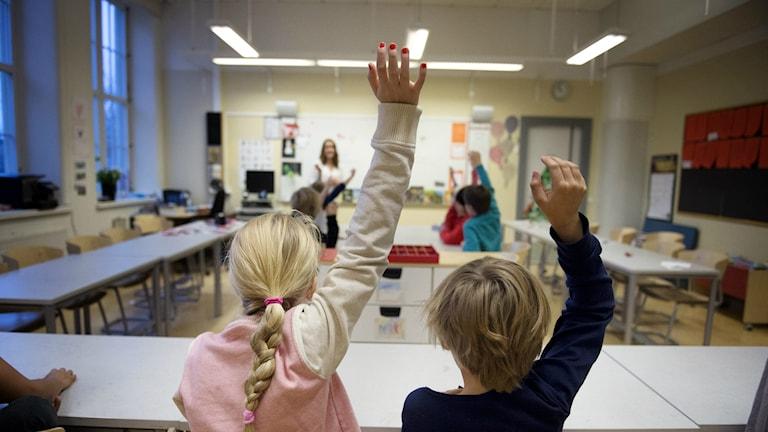 Barn räcker upp handen i klassrum