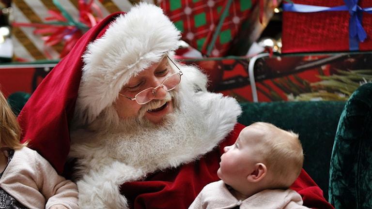 Ein typischer Weihnachtsmann lächelt einen Säugling an. Auch in Schweden ist Glücklichsein zu Weihnachten oberstes Gebot (Foto: AP Photo/Robert F. Bukaty)