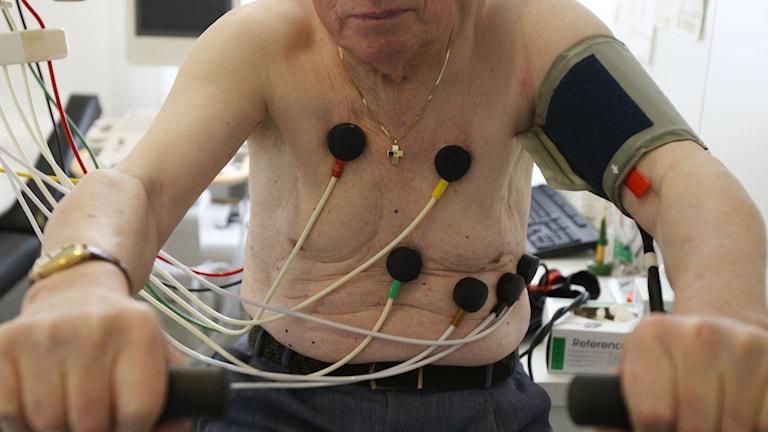 En äldre man som genomför ett EKG- test.