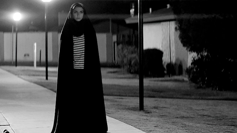 Flicka går ensam efter trottoar i natten