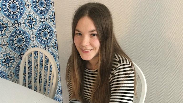 Emelia Johansen sitter framför ett bord.