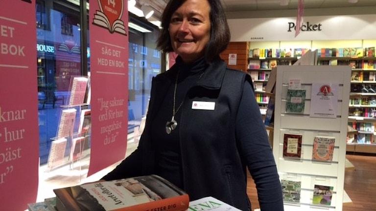 Ann-Charlotte Carlsson framför böcker som säljer