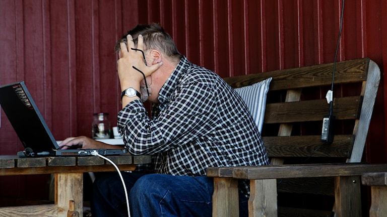 En äldre man sitter framför en laptop.