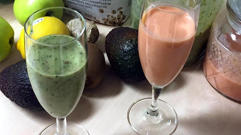 Två champangeglas med olika smoothies, i bakgrunden ligger frukt, grönsaker och havregryn